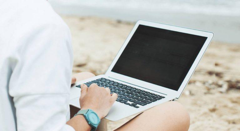 Eine Bloggerin am Strand tippt gerade etwas auf ihrem MacBook.