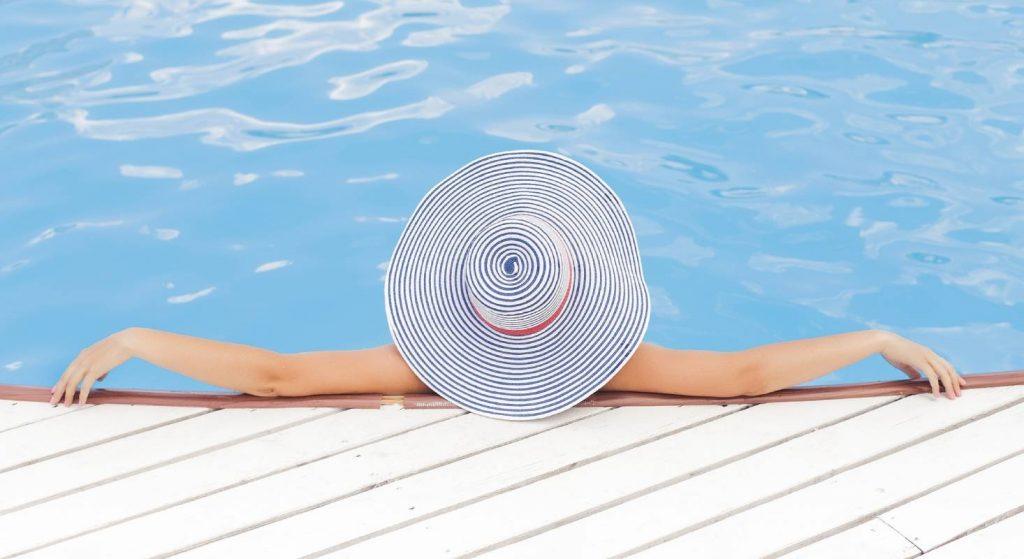 Eine Frau liegt am Pool ohne Mobilgerät. Sie ist also offline.
