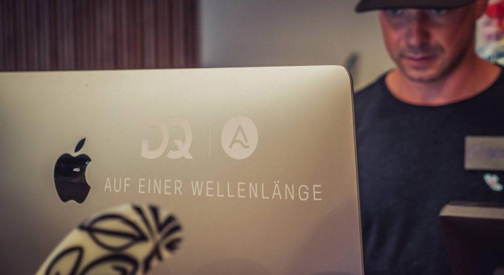 Ein Mitarbeiter von OANA hinter dem iMac.