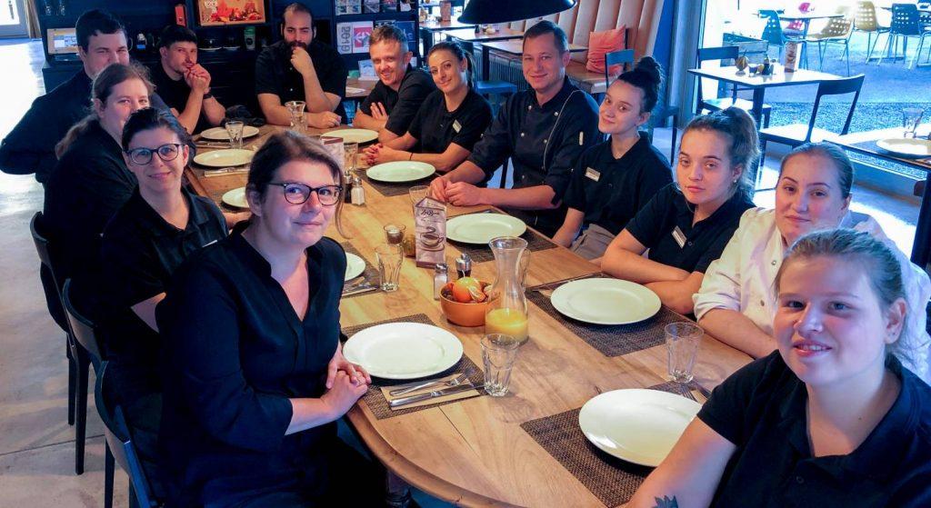 Das Team vom ZwiBack sitzt an einem langen Tisch und alle essen zusammen.