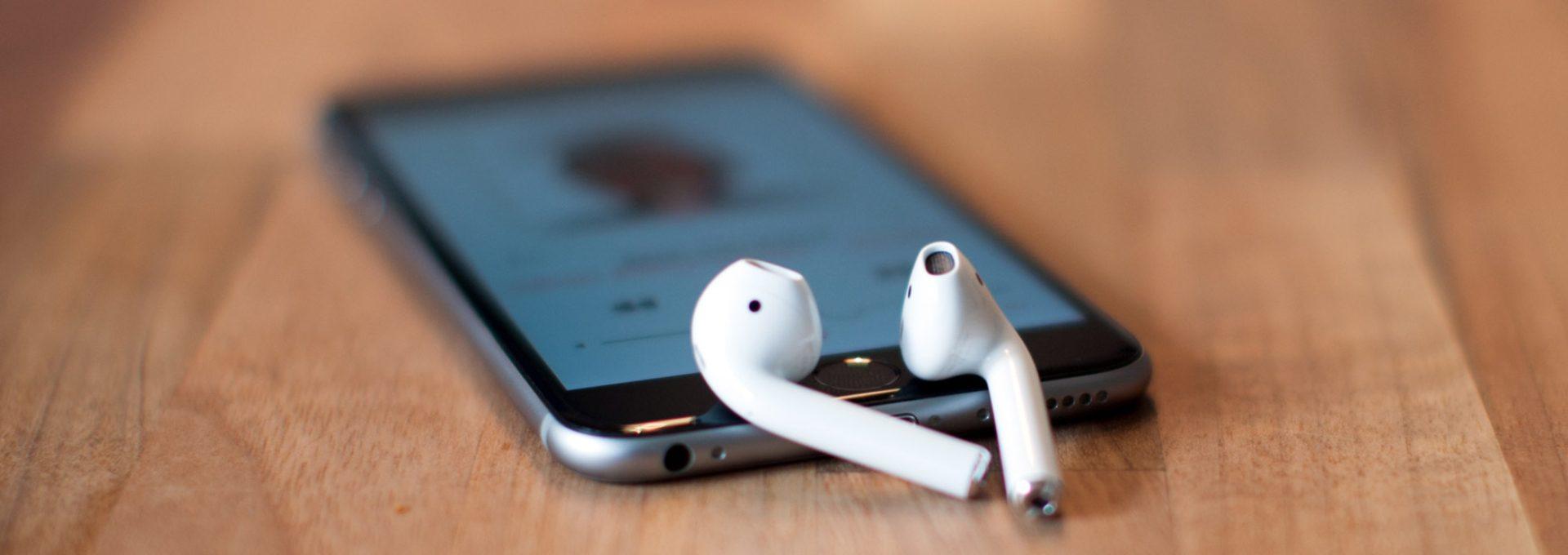 Die Grösse der AirPods ist im Vergleich mit dem dazu gelegten iPhone ersichtlich. Weiter ist die Form der InEar Kopfhörer klar erkennbar.