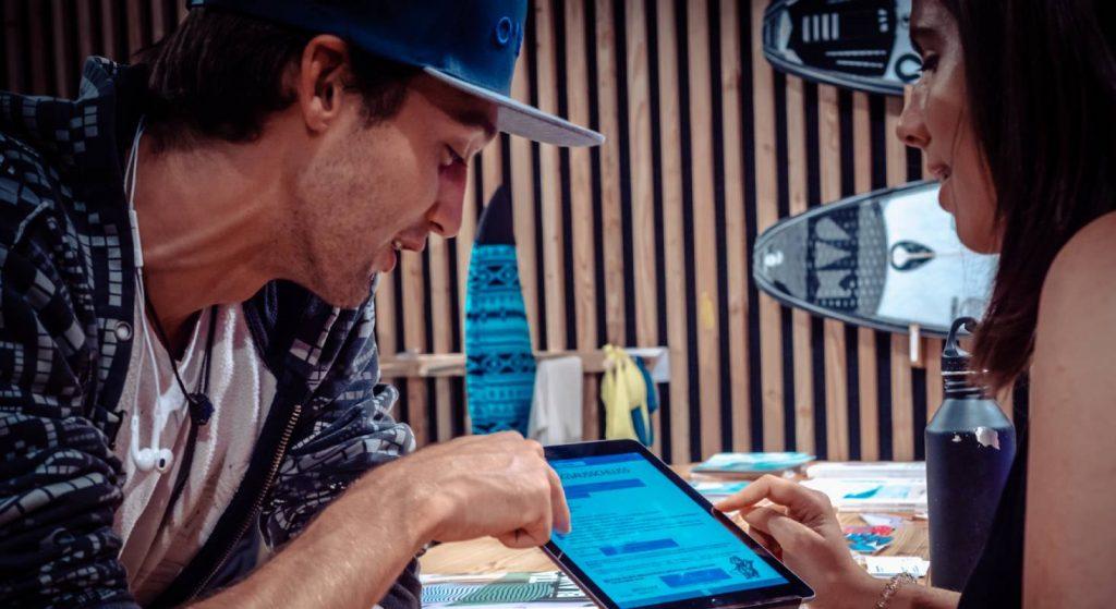 Ein Mitarbeiter von OANA erklärt einer Kundin am iPad, wi sie sich registrieren kann.