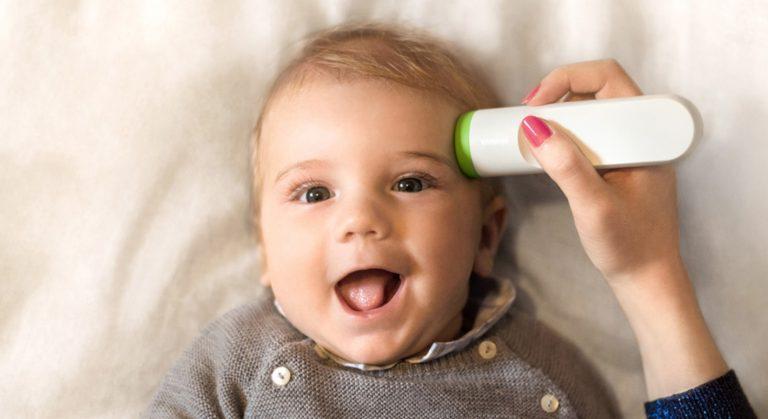 Das Bild veranschaulicht, wie der Withings Thermo an der Schläfe eines Kindes platziert wird, um die Temperatur zu messen.