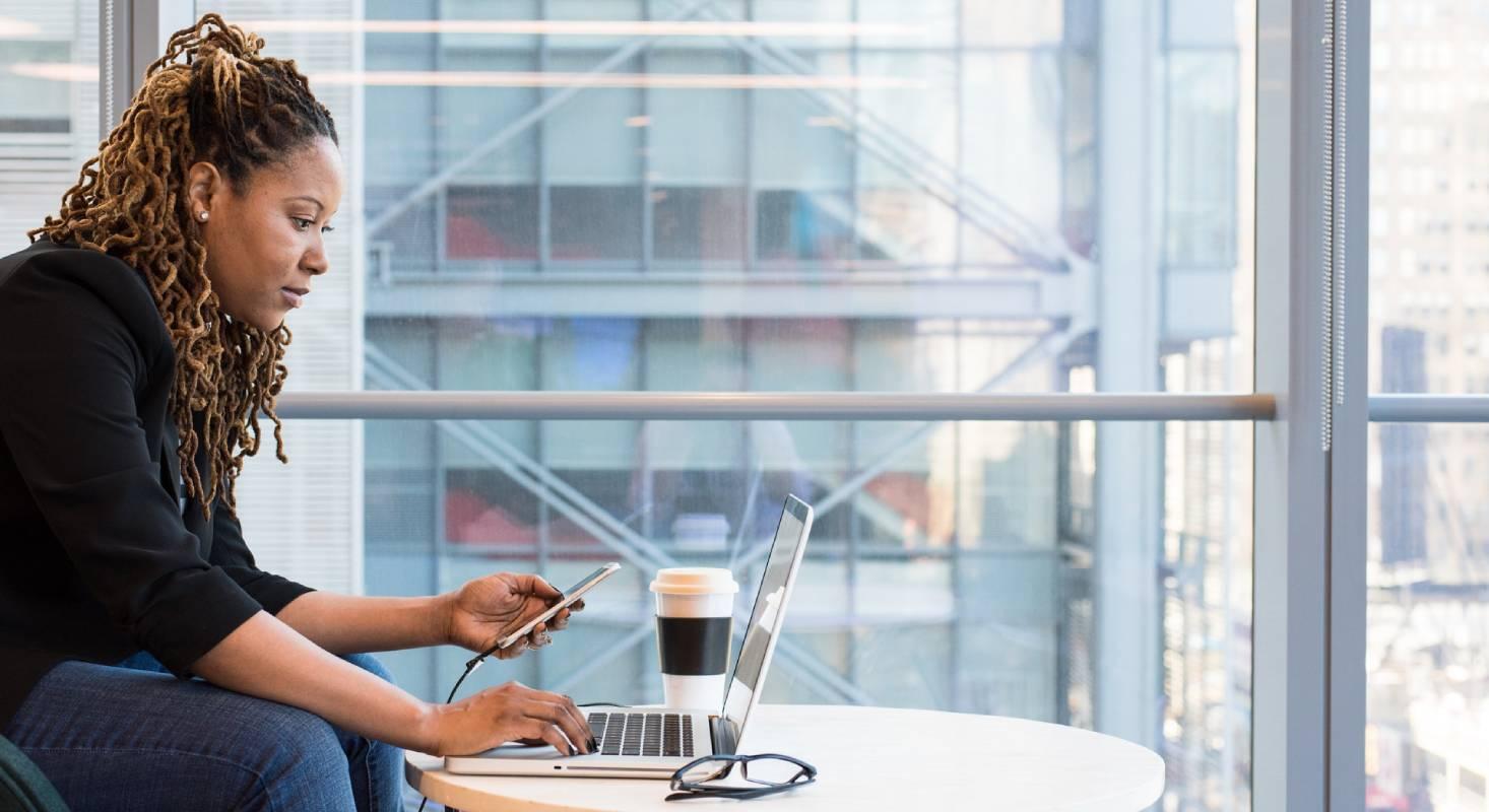 Veranschaulichung einer digital unabhängigen Frau bei der Arbeit mit dem MacBook und dem iPhone