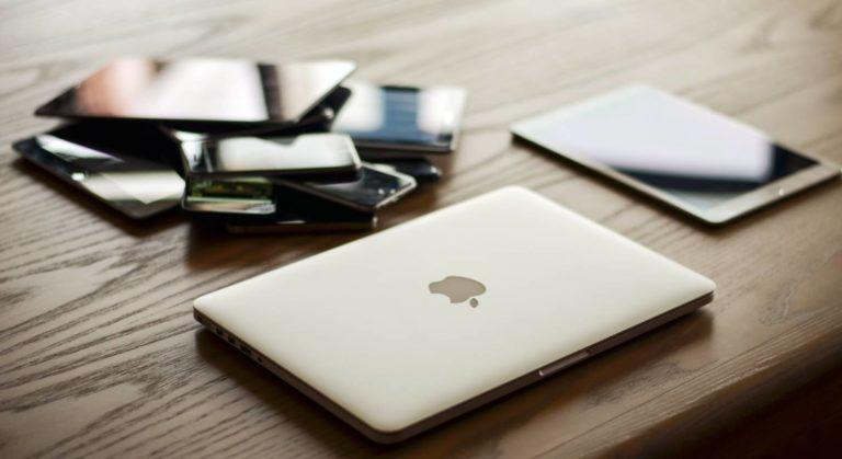 MacBook und iPad sowie ein Stapel weiterer Geräte stellen dar, dass alte Geräte irgendwo herumliegen, obwohl man sie entsorgen könnte.