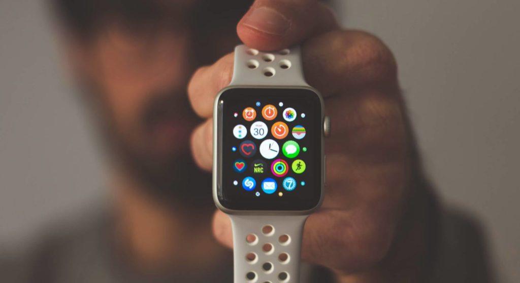 Ein Mann zeigt, wie das Menü auf der Apple Watch aussieht indem er sie in die Kamera streckt.